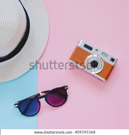 Creative Flat lay fashion style with camera, sunglasses and panama hat on pastel color background