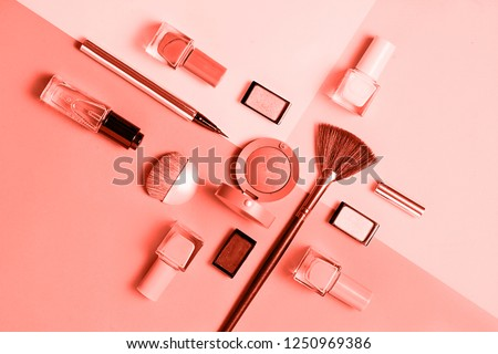 Creative flat lay of fashion bright nail polishes and decorative cosmetic on a colored in color of year 2019 Living Coral background. Macro color 16-1546 background. Beauty blogger concept. Top view #1250969386