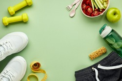 Creative flat lay of sport and fitness equipments. Women's white sneakers, water bottle, sportswear, dumbbells and lunchbox with healthy vegetable salad, on light green background.