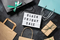 Creative flat lay overhead view of Black Friday Sale text on the lightbox, Paper bags and gift boxes on black background.