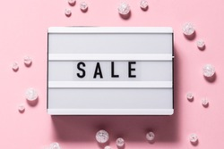 Creative flat lay overhead view of Sale text on the lightbox and shining decorations on pink background. Festive Sale and Promo concept. Black Friday concept.