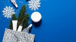 Creative flat lay overhead view of skin care cosmetic in unbranded containers in silver shopping bag with Christmas decorations. Skin care in winter time concept. Christmas cosmetic sale banner.