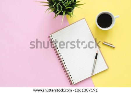 Creative flat lay photo of workspace desk. Top view office desk with mock up notebooks, plant, coffee cup and copy space on pastel color background. Top view with copy space, flat lay photography.