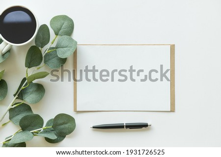 Creative flat lay photo of workspace desk. top view office desk with mock up white paper, coffee, pen, plant branches on white background. Workspace concept. Top view, copy space, mockup, flat lay.