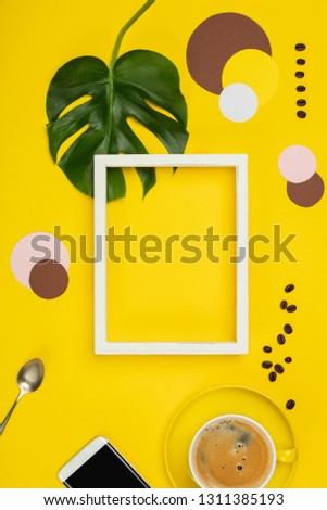 Creative flat lay with cup of coffee, paper circles, mobile phone, tropical plant and white frame for your text on yellow background
