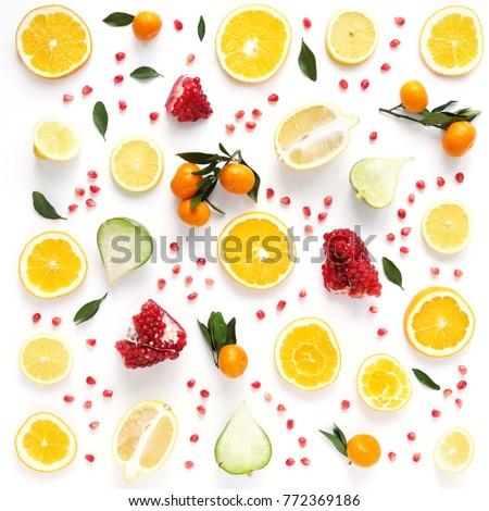 Creative flat layout of fruit, top view. Sliced orange, lemon, pomegranate, tangerine, green leaves isolated on white background. Food wallpaper, composition pattern of fresh fruits.