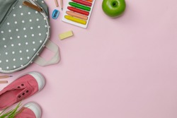Creative flatlay of education pink table with backpack, student books, shoes, colorful crayon, empty space isolated on pink background, Concept of education and back to school