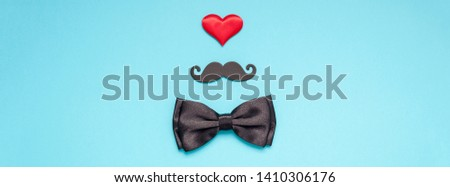 Creative flatlay overhead top view retro stylish black paper moustaches bow tie red heart turquoise background copy space. Men health awareness month fathers day masculinity concept long wide banner #1410306176