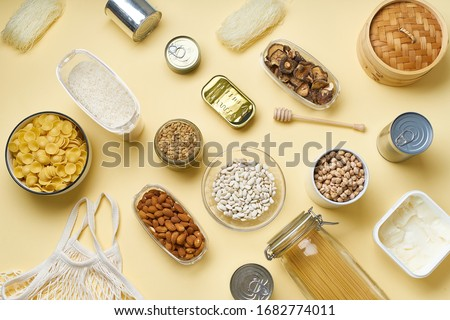 Creative flatlay with pantry staples. Glass jars with pasta, beans and chickpeas, canned goods, nuts and dried mushrooms in reusable containers. Top view pattern with basic products  Stockfoto ©