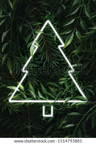 Creative fluorescent Christmas  layout made of leaves, branches and Christmas tree neon sign. Flat lay. Nature concept.