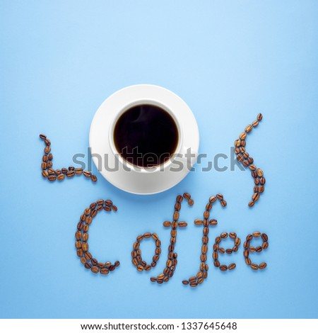 Creative food concept photo of cup of coffee drink beverage with sign made of beans on blue background.