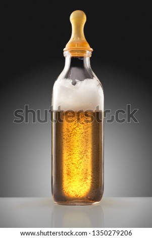 Creative food concept photo of feeding baby children bottle with nipple full of beer alcohol spirits as a milk replacement for babies. #1350279206