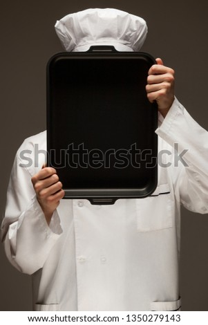 Creative food concept photo portrait of cook chief baker hiding his face behind the kitchenware baking sheet tray pan on brown background.
