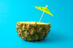 Creative food health diet concept photo of pineapple drink beverage juice cocktail with umbrella on blue background.