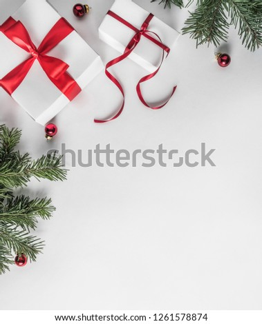 Creative frame made of Christmas fir branches on white paper background with red decoration, gift boxes. Xmas and New Year theme. Flat lay, top view #1261578874