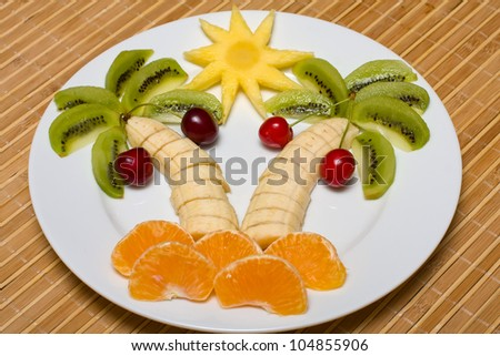Creative fruit dessert with kiwi, banana,cherry and orange palm tree shape