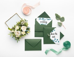 Creative green envelopes with white wedding invitations and small bouquet of flowers on white background