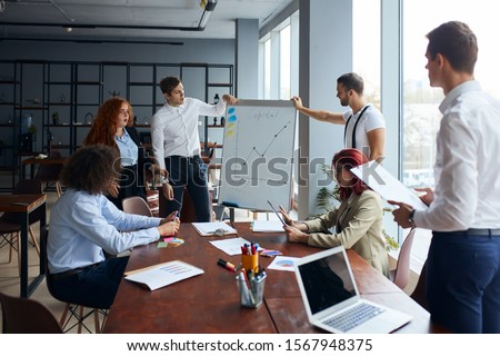 Creative group of business coworkers discuss ideas using flipchart and laptops, active discussion and explaining in office