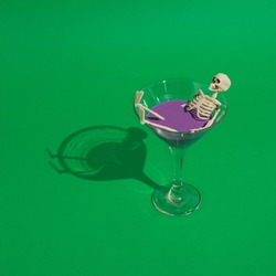 Creative Halloween arrangement made of a glass of drink and skeleton on a green background. Halloween party concept.