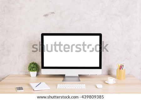 Creative hipster desktop with blank white computer screen, coffee cup, smart phone and other items on concrete background. Mock up