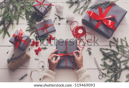 Creative hobby. Gift wrapping. Packaging modern christmas present boxes in stylish gray paper with satin red ribbon. Top view of hands on white wood table with fir tree branches, decoration