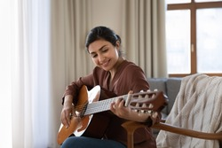 Creative hobby. Talented young mixed race female musician sit in armchair alone compose instrumental song using classic guitar. Smiling biracial lady play calm melody on musical instrument. Copy space