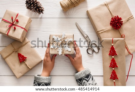 Creative hobby. Woman\'s hands show christmas holiday handmade present in craft paper with twine ribbon. Making bow at xmas gift box, decorated with snowflake. Scissors on white wooden table, top view.