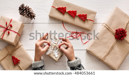 Creative hobby. Woman\'s hands wrap christmas holiday handmade present in craft paper with twine ribbon. Making bow at xmas gift box, decorated with snowflake on white wooden table, top view.