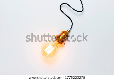 Creative idea concept, designer lamp, modern interior item. Vintage fashionable edison lamp on light gray background. Top view flat lay copy space. Lighting, electricity, background with lamp