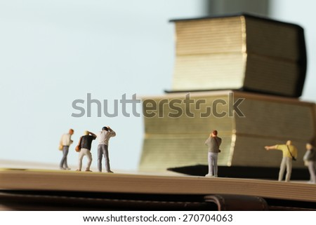Creative idea concept - miniature photographer with vintage golden book on open paper notebook #270704063