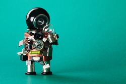 Creative idea concept. Robot looking at light bulb. retro style toy character with funny black helmet head. Copy space, green background