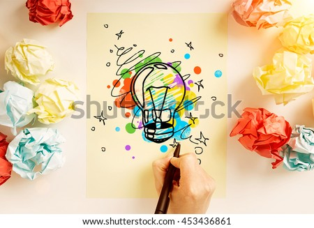 Creative idea concept with hand drawing abstract lightbulb sketch on paper sheet surrounded with colorful crumpled paper balls