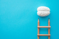 Creative idea, imagination, design and invention concept. Flat lay minimal style of staircase pencils and smart brain cloud on blue pastel background with copy space. Outstanding idea is attractive.