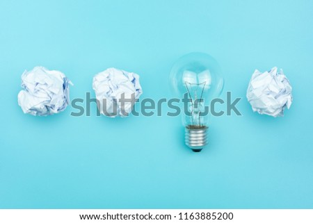 Creative idea, Inspiration concept with light bulb and crumpled paper balls on blue background. #1163885200