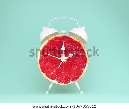 Creative idea layout fresh grapefruit slice alarm clock on pastel blue background. minimal idea business concept. fruit idea creative to produce work within an advertising marketing communications #1069353812