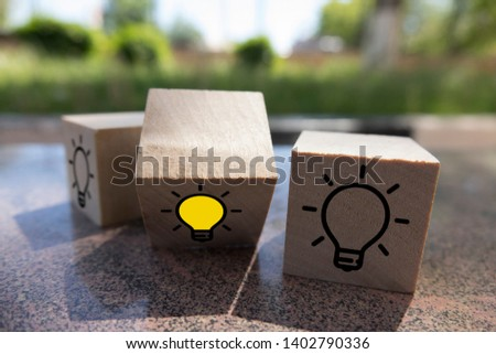 Creative idea, New idea, innovation and solution concept. wooden cubes with the yellow light bulb symbol on table, blue background, copy space