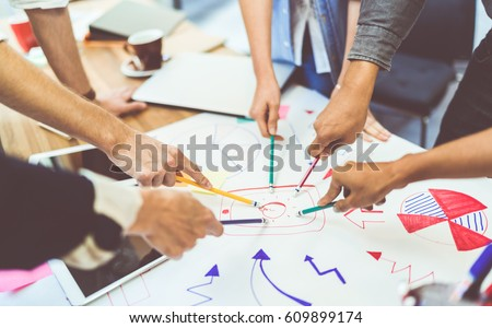 Creative idea teamwork concept. Group of multiethnic diverse team, business partner, or college students in project meeting at modern office. Five people pointing at lightbulb drawings.