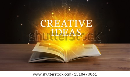 CREATIVE IDEAS inscription coming out from an open book, educational concept