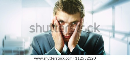 Creative image of attractive male touching his face in trouble