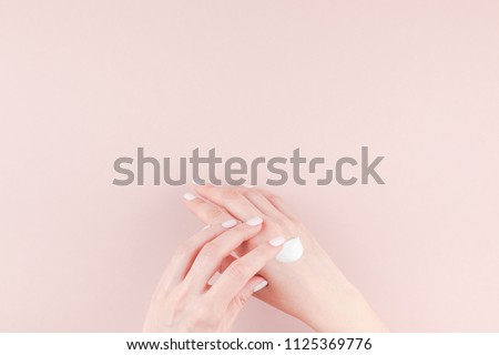 Creative image of woman moisturizing her hand with cosmetic cream lotion with copy space on millennial pink background in minimalism style. Concept template feminine blog, social media, beauty concept #1125369776