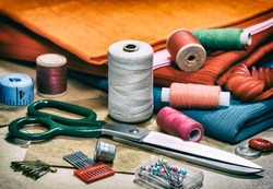 Creative image. Sewing threads for sewing and various accessories for needlework. A set of sewing accessories for sewing, spools of thread, fabrics, scissors and a thimble close-up. Retro style