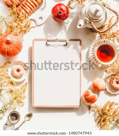 Creative inspiration and ideas autumn flat lay with blank clipboard on white desk with  pumpkin, apples, mini donuts, pastry , teapot, cup of tea and flowers. Top view. Fall layout. Sunny day.