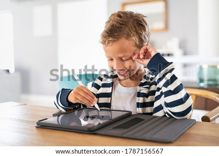 Creative kid drawing on tablet using digital pen. Child using pen on tablet to draw and complete homework. Cute little boy using stylus on screen and drawing pictures at home. Foto stock ©