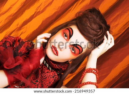 Creative lady.Young woman in dramatic image and with red and black artistic visage. #216949357