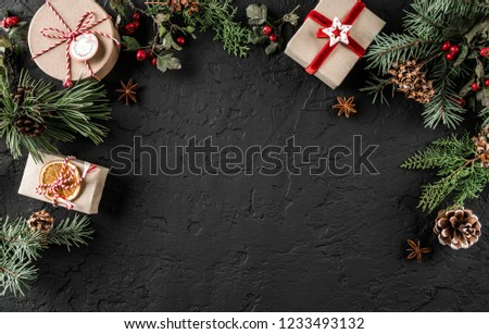Creative layout frame made of Christmas tree branches, pine cones, gifts on dark background. Xmas and New Year theme, snow. Flat lay, top view, wide composition #1233493132