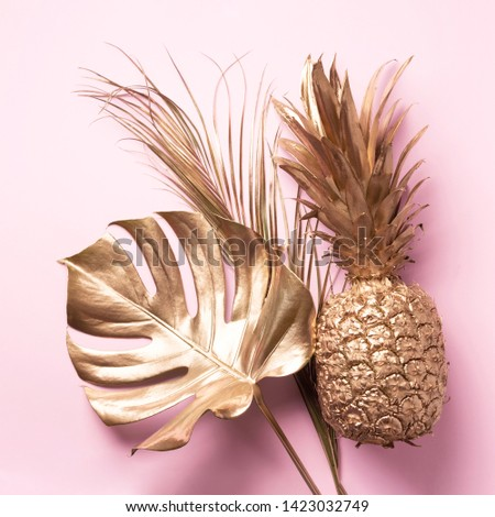 Creative layout. Gold pineapple and golden palm, monstera on pink background with copy space. Top view. Tropical flat lay. Exotic food concept, crazy trend. Banner. #1423032749