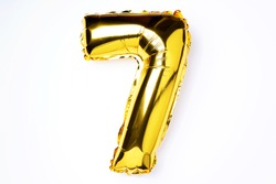 Creative layout. Golden foil balloon number and digit seven 7. Birthday greeting card. Anniversary concept. Top view. Copy space. Stylish gold numeral over white background. Numerical digit