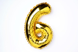 Creative layout. Golden foil balloon number and digit six 6. Birthday greeting card. Anniversary concept. Top view. Copy space. Stylish gold numeral over white background. Numerical digit
