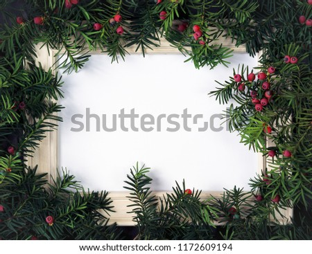 Creative layout made from Christmas tree branches with red berries and frame paper card note. Copy space for text. Nature New Year concept. Flat lay. #1172609194