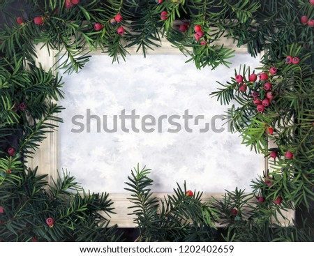 Creative layout made from Christmas tree branches with red berries and frame with snowflakes for paper card note. Copy space for text. Nature New Year concept. Flat lay. #1202402659